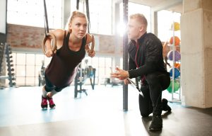 Woman exercising with a trainer at the gym