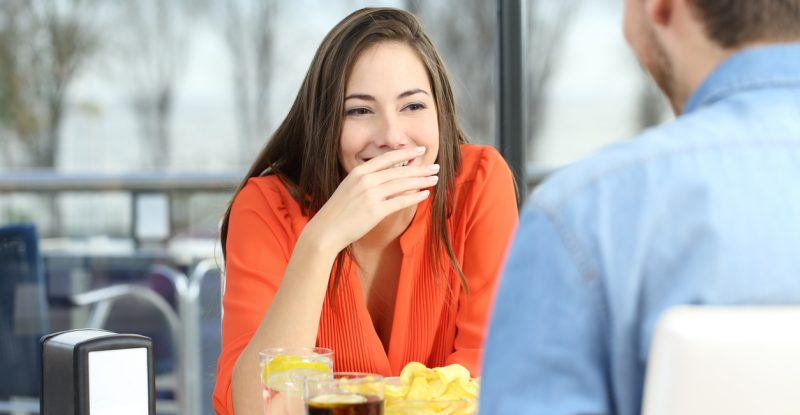 Woman covering her mouth to hide smile or breath