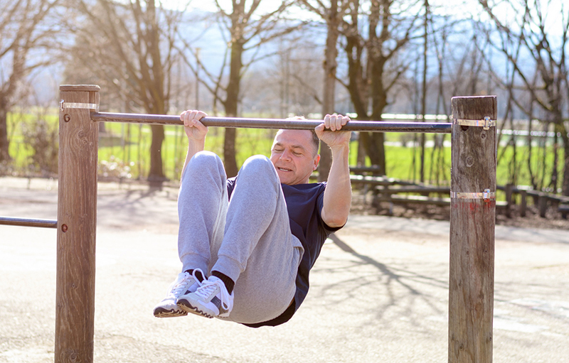 Middle-aged man working out on a horizontal bar