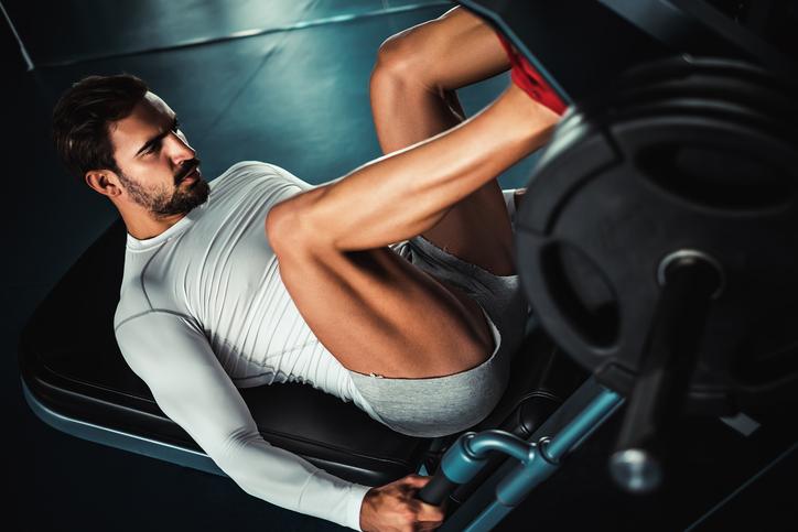 Man training legs on leg press machine