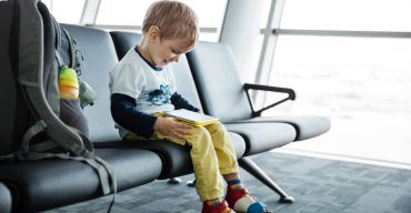Little boy playing on his tablet in airport