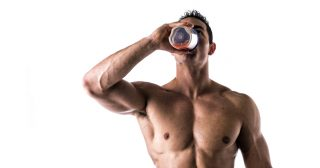 Muscular shirtless male bodybuilder drinking protein shake from blender