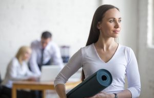 Business woman with yoga mat