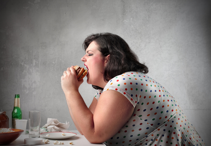 An obese woman eating a hamburger and being gluttonous