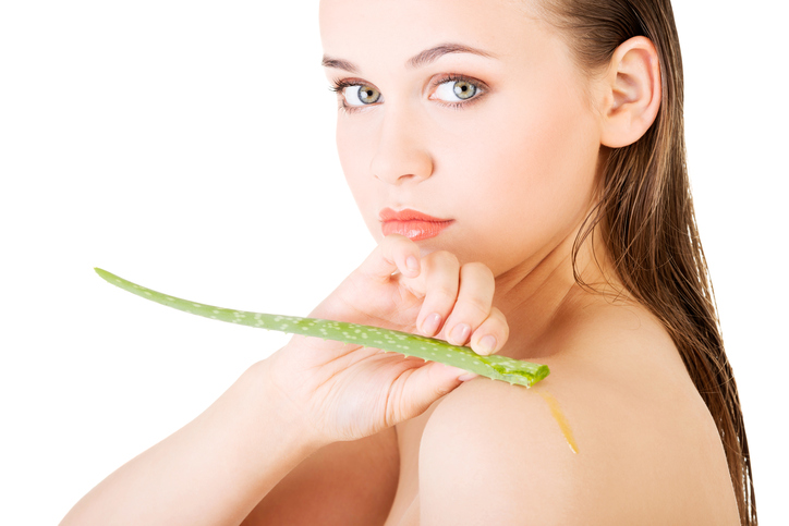 Bare shouldered woman rubbing aloe vera leaf on her shoulder