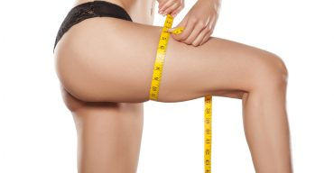 Young woman measures her leg with a measuring tape