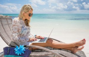 Businesswoman with computer on the beach