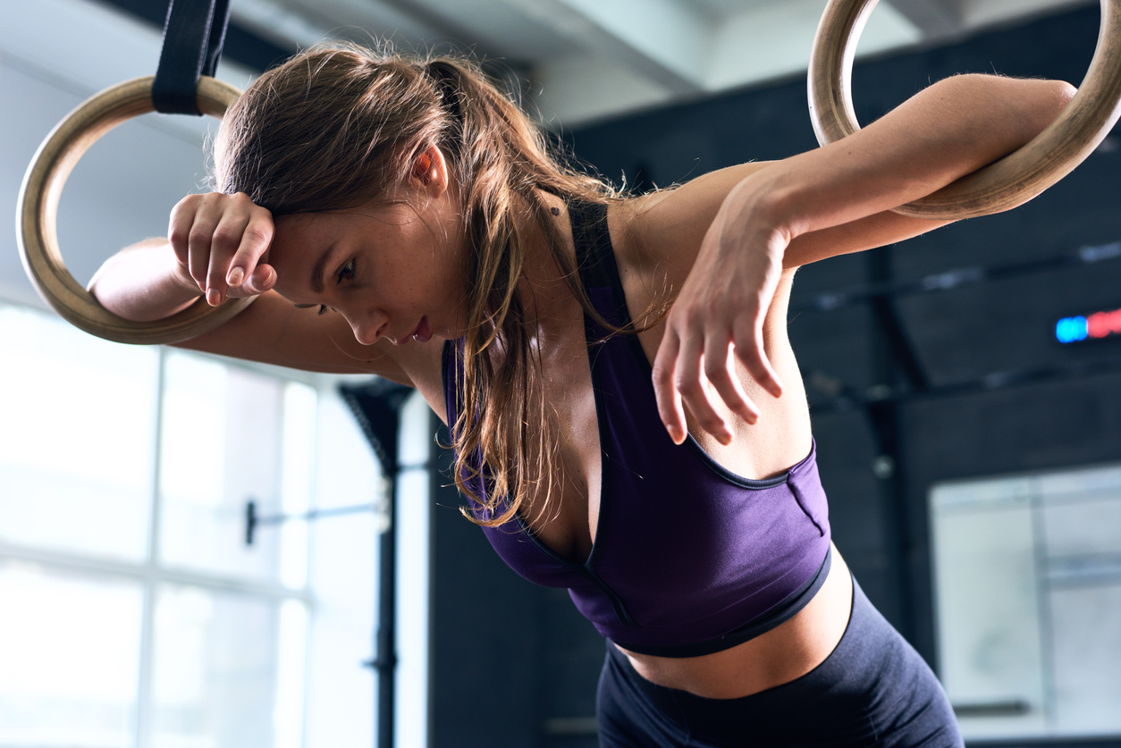 Exhausted Woman Training on Gymnastic Rings