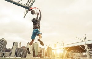 Basketball street player making a rear slam dunk.