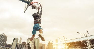 Basketball street player making a rear slam dunk.