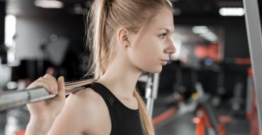 Young blonde woman doing exercises with barbell in gym