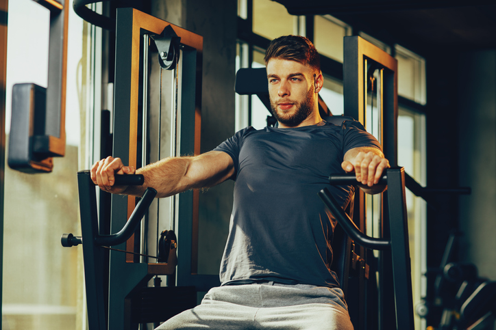 Handsome man in the gym doing chest exercise