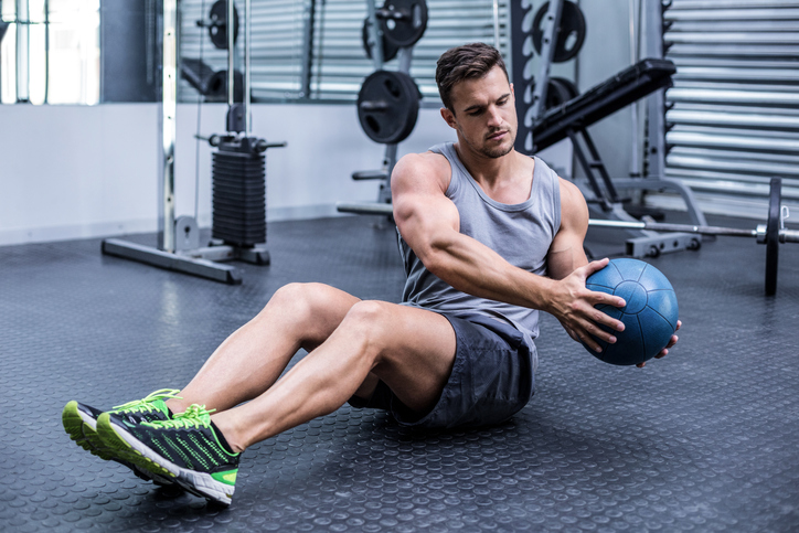 Muscular man doing russian twist exercises