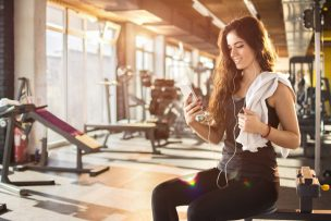 Attractive girl with earphones listening to music in gym.