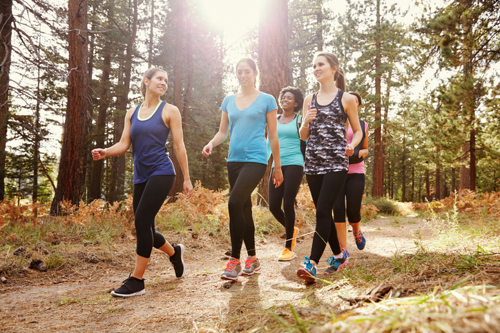 Group of women runners walking in a forest talking