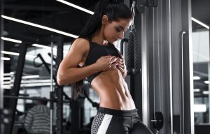 Fitness sexy woman showing abs and flat belly. Beautiful muscular girl, shaped abdominal