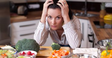 A frustrated woman looking out at salad bowls in her kitchen