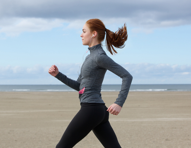Young woman running by the beach