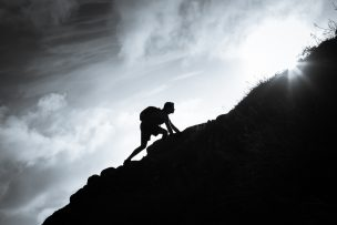 Man climbing up a mountain.