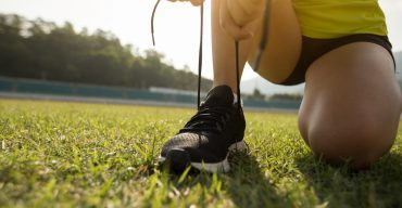 Young fitness woman runner tying shoelace on stadium tracks