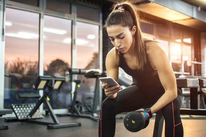 Young woman using phone at gym.